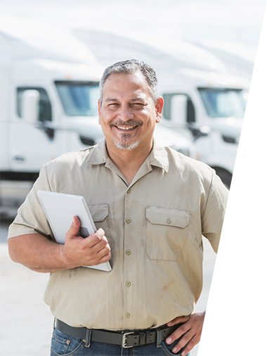 Photo of fleet manager smiling at camera and standing in front of trucks.